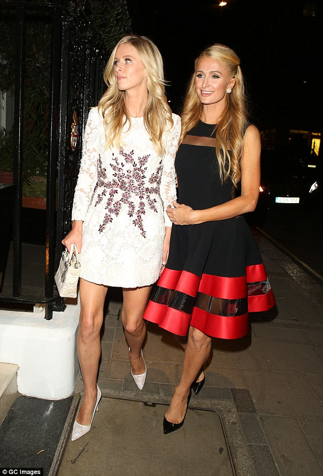 Lovely ladies: Paris looked delightful in a flirty black A-line dress, while Nicky kept it clean in bridal white