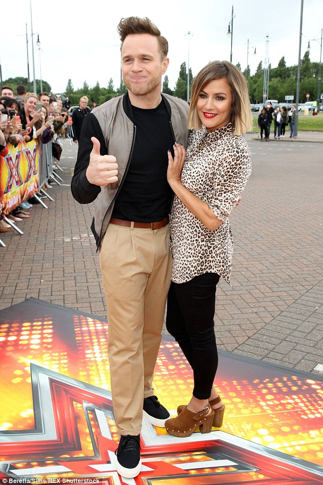 Thumbs up: Olly looked cool in varsity jacket, black top, khaki trousers and a pair of platform plimsolls