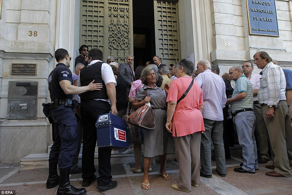A security worker carries cash into a bank as Greek pensioners line up to get part of their pensions in Athens