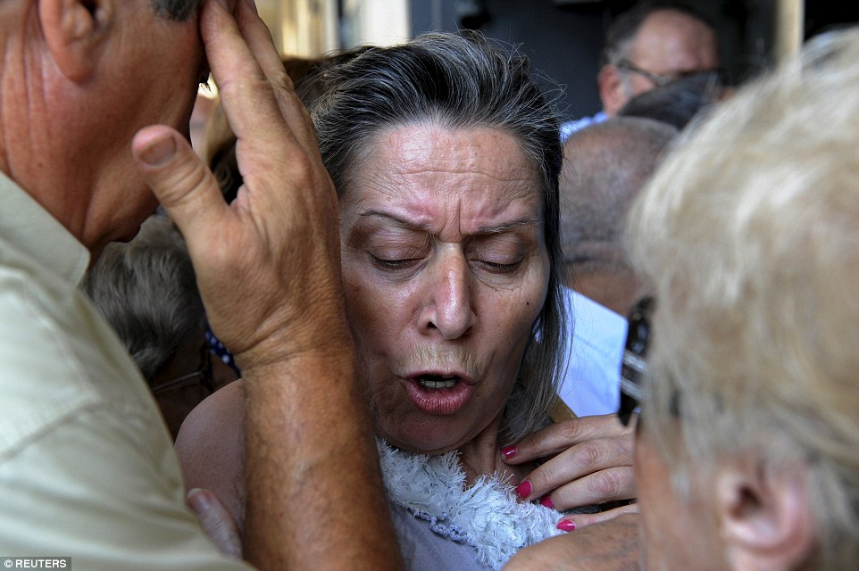A pensioner reacts as she tries to enter a National Bank branch to receive part of her pension in the city of Thessaloniki this morning