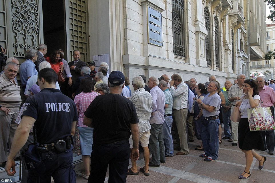 A policeman maintains order as Greek pensioners, who do not own ATM cards, line up to withdraw their pensions in Athens today