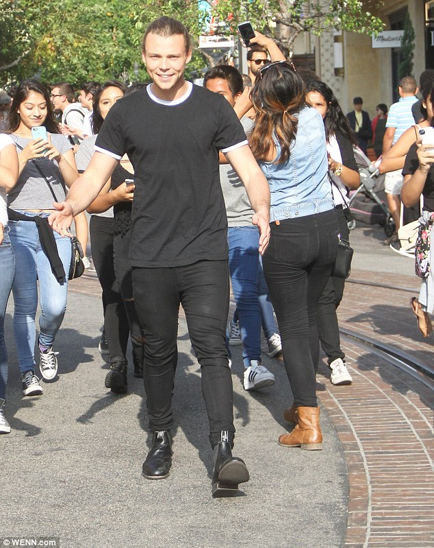 He's got fans: Ashton was mobbed by a group of girls who eagerly held up their camera phones for a photo