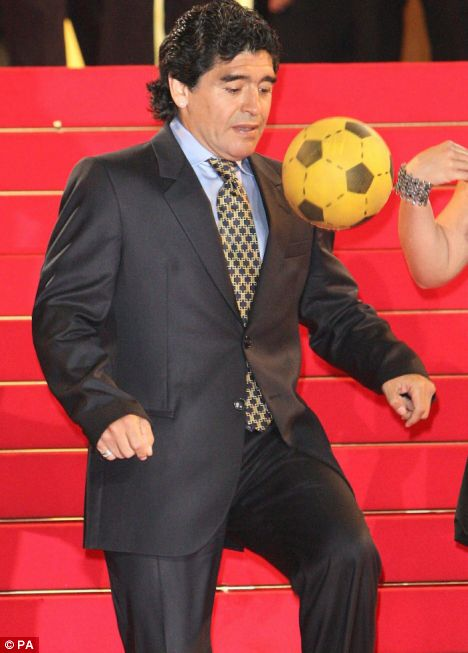 Maradona plays with a football as the crowd looks on
