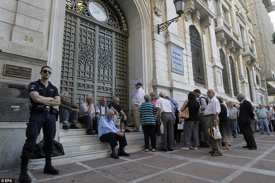 Waiting to open: A policeman maintains order as Greek pensioners line up to withdraw their pensions in Athens today