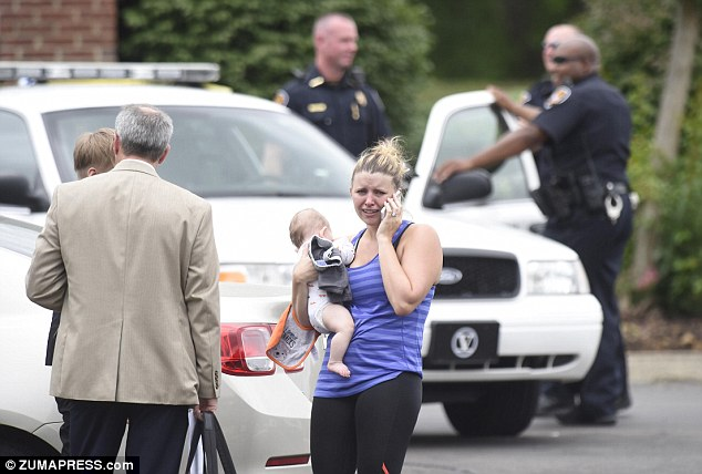 Abbey Harris makes a phone call while holding her son at the scene of a police investigation after she was kidnapped along with her bank manager husband, Tanner, who was forced to rob his own branch