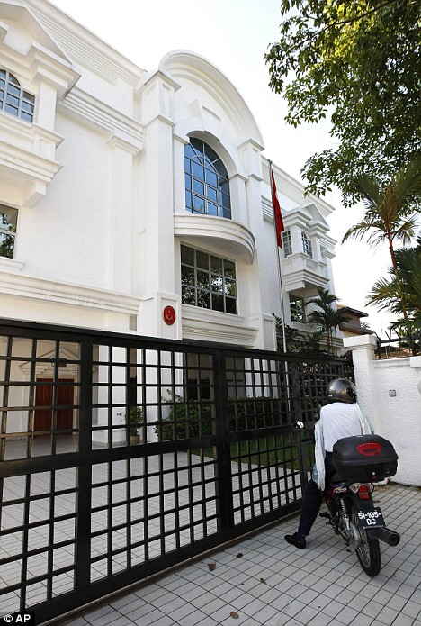 Hiding place: A messenger waits outside Turkish Embassy where opposition leader Anwar Ibrahim is hiding in Kuala Lumpur