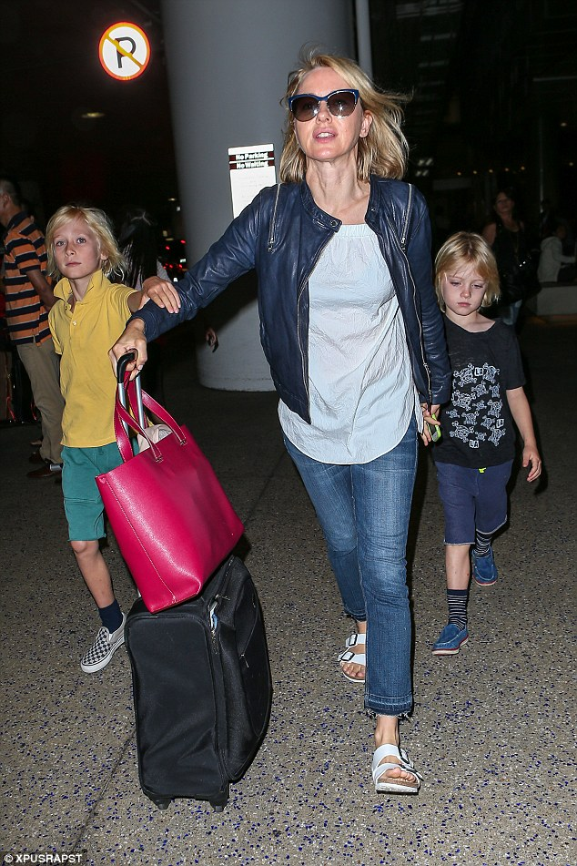 Mummy's boys: Naomi's two sons held on to her as they made their way through LAX