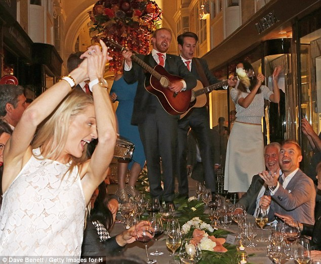 Fun couple: Ronan looked delighted as his fiancee threw herself into the dancing as the band played on the table
