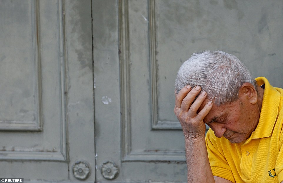 Hopeless: A pensioner sits with his head in his hands in front of the main entrance of a National Bank branch in central Athens