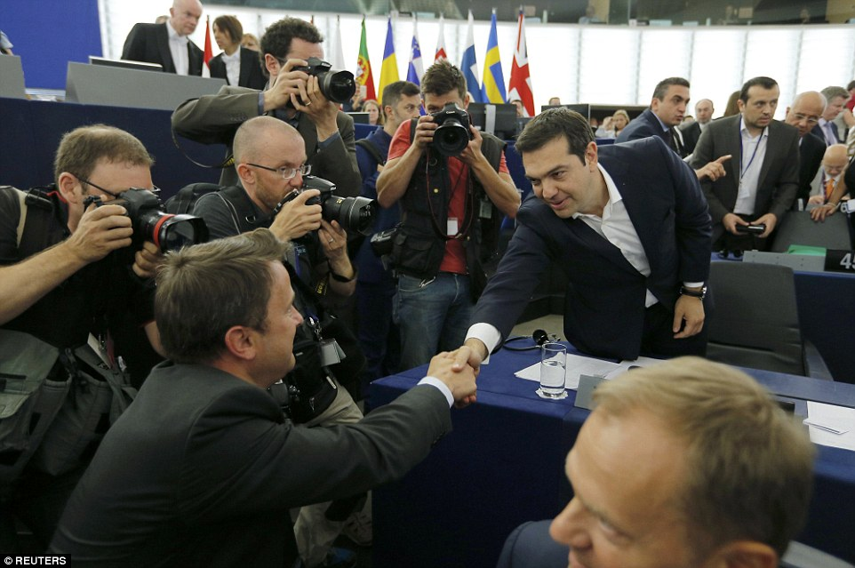 Prime Minister Alexis Tsipras shakes hands with a member of the European Parliament in Strasbourg during talks on Greece's economic crisis