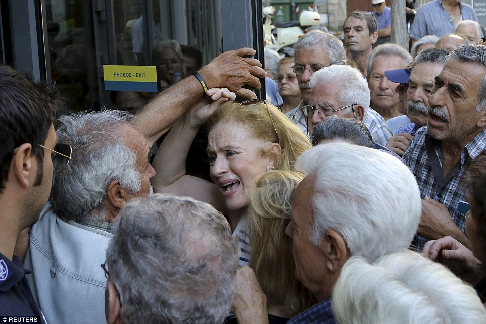 Desperate: Pensioners argue, push and shove as they tried to enter a National Bank of Greece branch in the city of Iraklio on Crete today