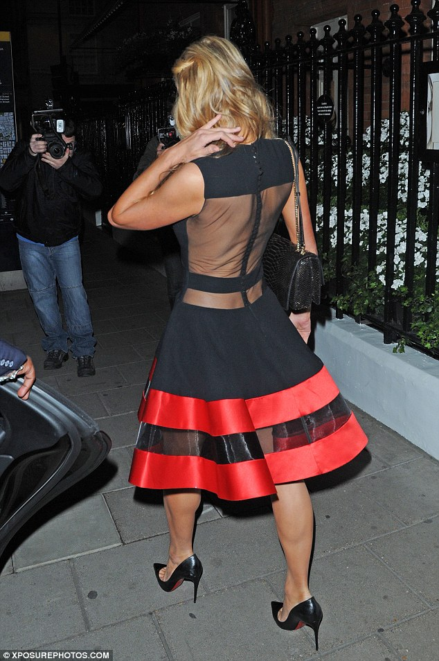 Elegant: Paris went braless on her way to dinner, matching red details to the bottom of her Louboutin shoes