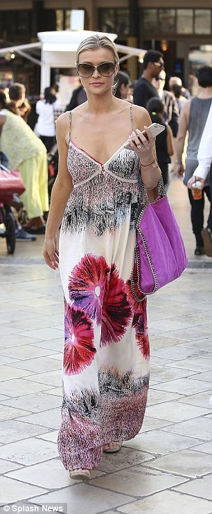 "The 5'7"" model added a splash of purple to her vibrant outfit, with a stylish chain strap bag slung across her arm"