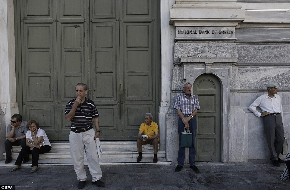 Greek pensioners wait outside of a National Bank of Greece branch in central Athens this morning