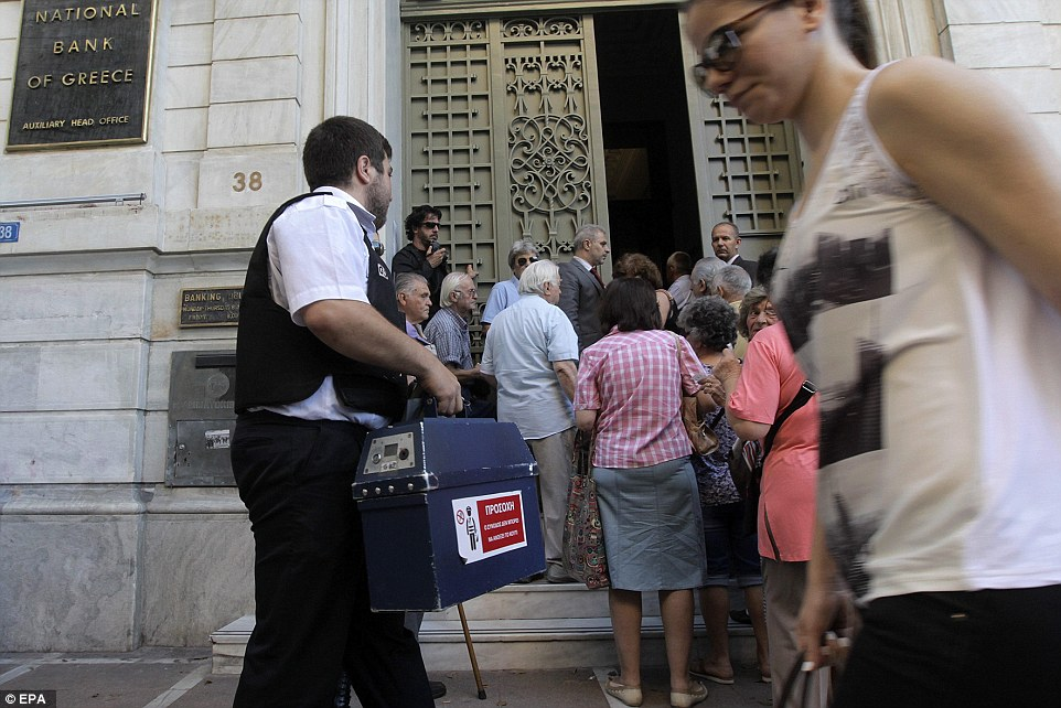 Enter: A security worker carries cash into a bank branch as Greek pensioners line up to get part of their pensions in Athens today