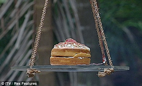 Here it comes: The delicious looking birthday cake is lowered towards the waiting celebrities...
