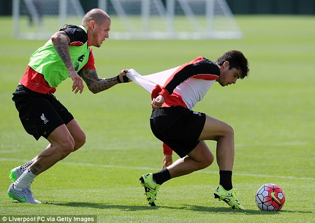 Liverpool defender Martin Skrtel tugs the shirt of Joao Teixeira as he competes the win the ball back