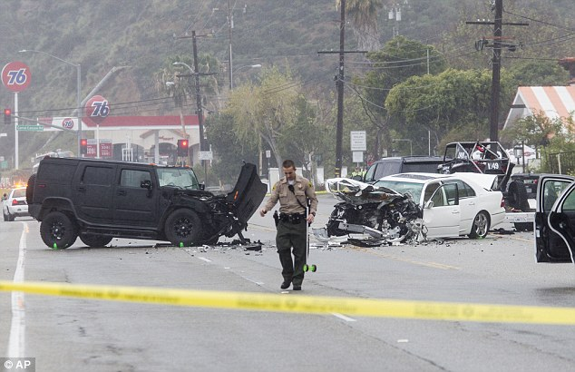 Clean-up: An LA County sheriff is pictured at the scene after the pile-up