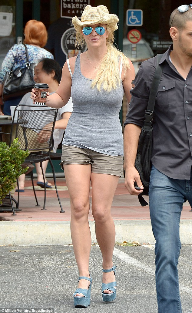 In shape: The Toxic hit-maker's tanned and toned legs were on full display in thigh-skimming khaki shorts, with her favourite towering blue wedge heels