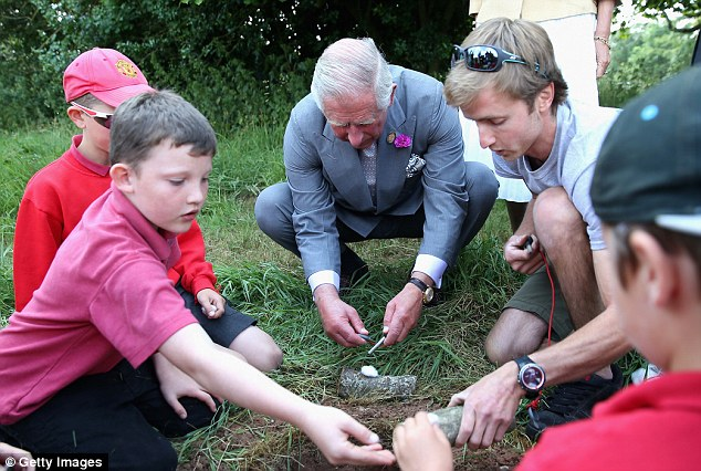 The royal looked like he was being taught how to make a camp fire with the group of children