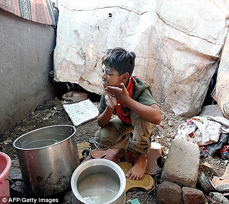 Azharuddin washes his face in a bowl of cloudy water, surrounded by piles of rubbish