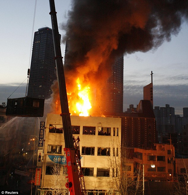 Police used a crane and a container box to set officers down on the roof of the building. The blaze is thought to have begun after squatters hurled Molotov cocktails