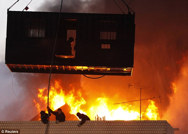 Squatters engulfed in flames on top of the Seoul building where five people are believed to have perished