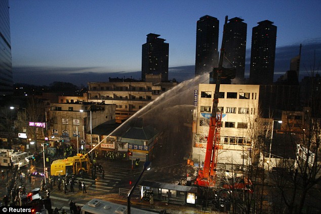Emergency services extinguished the flames using water cannons as another police container box ascends to the top of the building