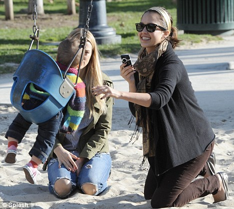 Not missing a moment: Jessica Alba snaps pictures of her daughter Honor Marie on her mobile phone as she spends the afternoon in Coldwater Canyon Park in California.