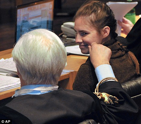 Knox smiles at her lawyer Luciano Ghirga prior to a defence hearing at the court in Perugia, Italy - the defence has begun its closing arguments, seeking to show that evidence in the case isn't sufficient to convict her