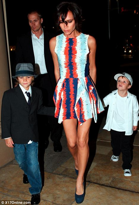 Devastated: Victoria Beckham, whose fashion line was stolen in a heist on Thursday, took sons Romeo and Cruz to a party in Beverly Hills yesterday