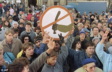 """Demonstrators carry a sign warning """"Police sticks prohibited"""" on the seventh day of the non-violent revolt in 1989"""