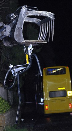 Torn open: The tractor grabber arm sliced through the top deck of the school bus