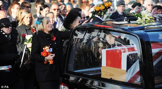 Corporal Loren Marlton-Thomas's wife Nicola steps forward to lay a flower on the hearse