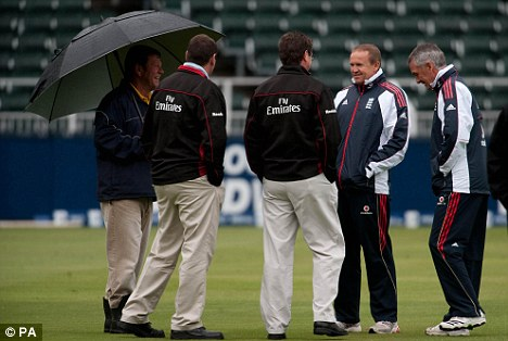 Wash-out: England coach Andy Flower and team manager Phil Neale (R) speak to the match umpires after inspecting the rain-soaked wicket at The Wanderers