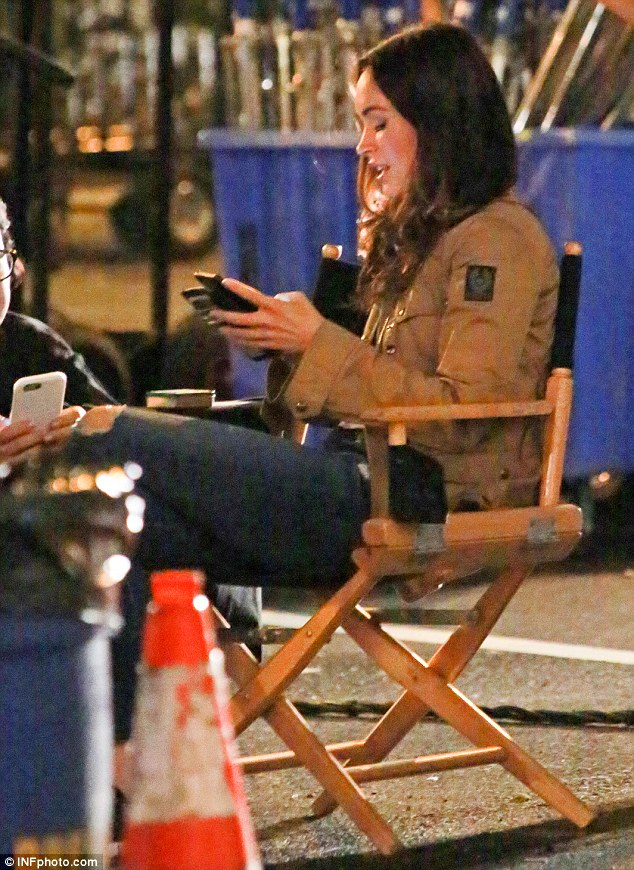 Time out: Megan chatted with members of the crew as she checked her phone in between takes
