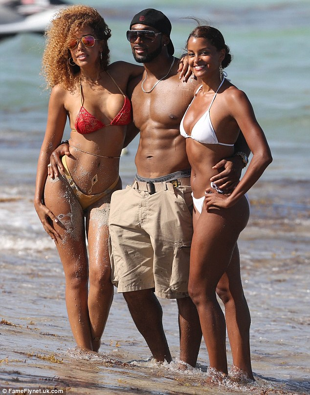 Lucky man: The two gal pals flanked a male companion as they posed for a photo together
