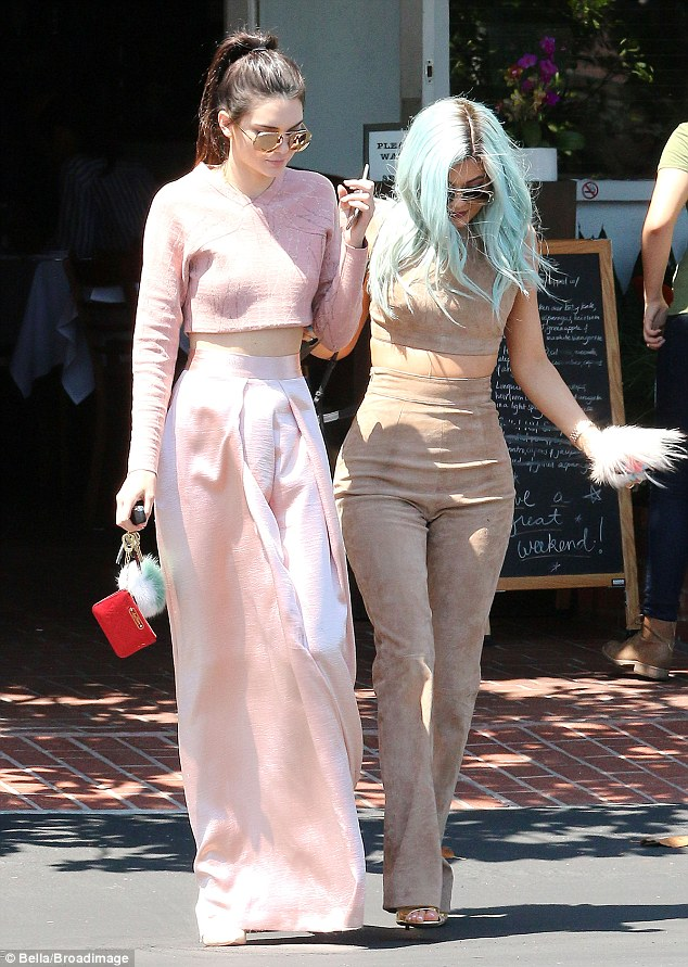 High style:Kendall, 19, wore a high-waisted pink skirt and matching crop top as she pinned her brunette locks back into a high pony tail