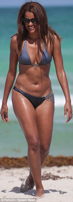Beach bum: Claudia was spotted on the beach the previous two days in a turquoise bikini on Thursday (left) ad a grey two-piece (right)