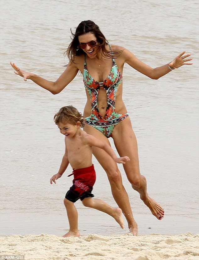 Fun games: Alessandra was seen chasing her little one across the sand and he looked particularly pleased