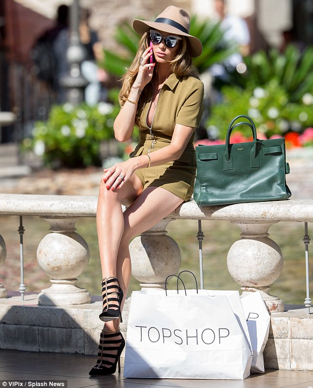 Checking in: The budding fashion designer looked incredible as she took time out from shopping to make a call