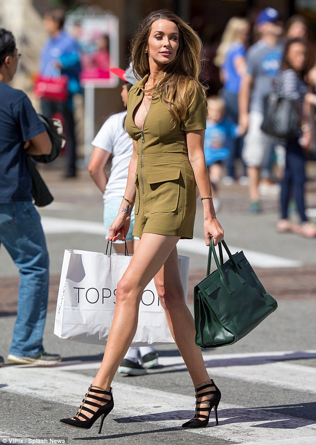 Leggy lady: The 29-year-old let her lengthy stems and busting cleavage do the talking as she modeled the khaki one-piece she designed herself