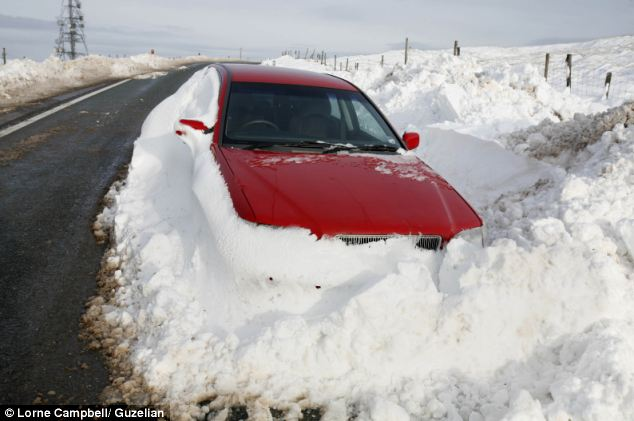 Bogged: A stranded car on Saddleworth Moor, near Oldham, Lancashire yesterday