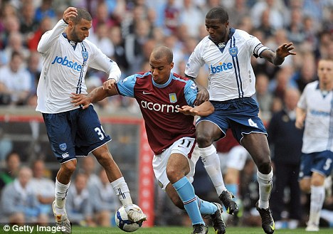Gabriel Agbonlahor of Aston Villa battles with Nadir Belhadj and Aaron Mokoena of Portsmouth
