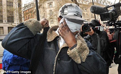 Ms DeBique covers her face as she arrives at the Central Employment Tribunal Court today