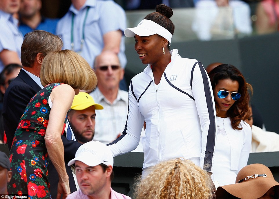 In the family: Venus Williams arrives in the player's box and is greeted by Anna Wintour as they watch her sister's battle on the court