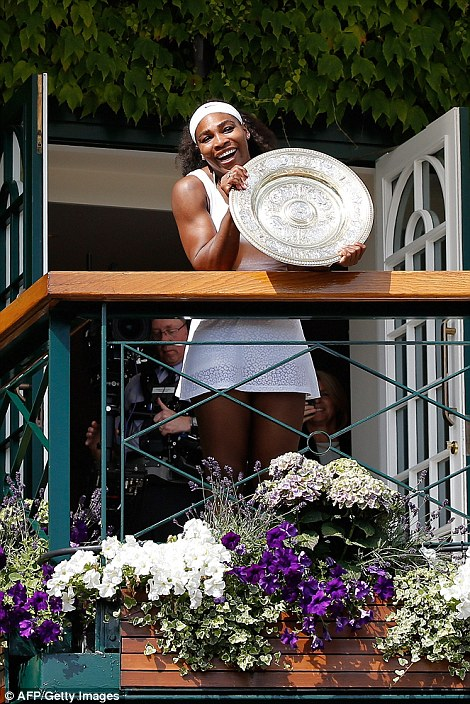 Triumph: Serena Williams shows off her trophy to the crowds from a balcony looking out over Centre Court after her decisive victory