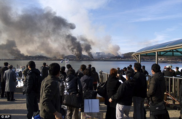 Shells: Terrified South Korean civilians watch artillery fire hit Yeonpyeong island last Tuesday in attacks that killed four people