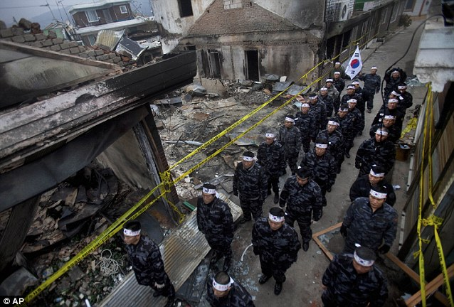Antagonising: South Korean military veterans demonstrate against North Korea in a the destroyed neighborhood on Yeonpyeong Island amid fears the country will be attacked again