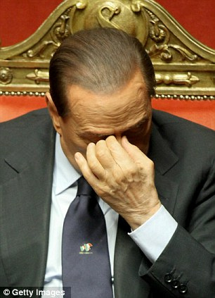 Pressure: He holds his head and later, right, looks pained as he addresses the Italian upper House